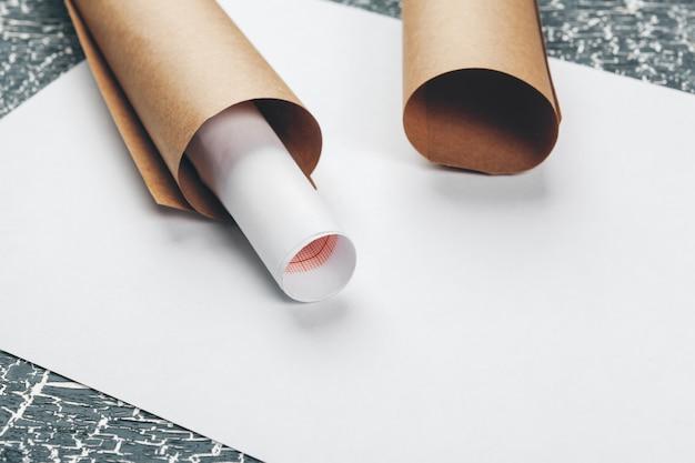 Planos arquitectónicos y rollos de planos y un instrumento de dibujo en la mesa de trabajo.
