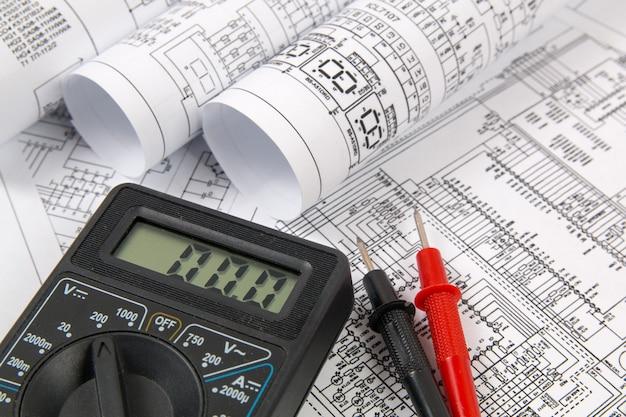 Planos de ingeniería eléctrica y multímetro digital.