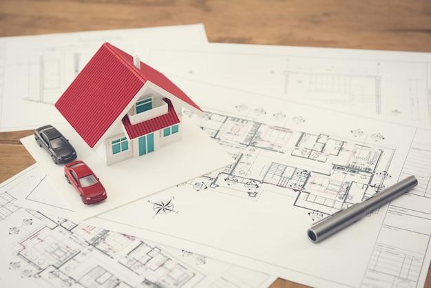 Planos y modelo de casa sobre la mesa