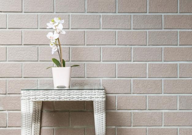 Planta artificial del primer con la flor blanca de la orquídea en la maceta rosada en la tabla de madera de la armadura en fondo marrón borroso de la textura de la pared de ladrillo