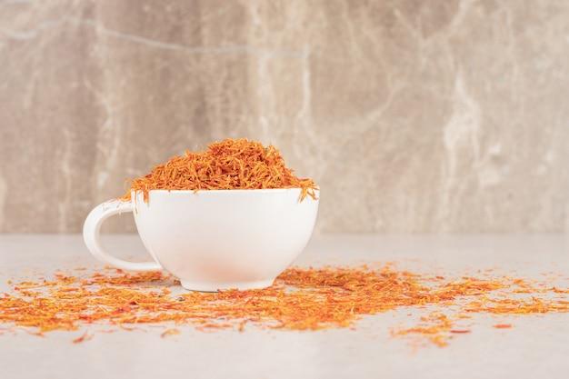 Planta de azafrán rojo en una taza sobre hormigón.