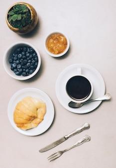 Planta de cactus; mermelada; arándano; taza de café y pan sobre fondo blanco.