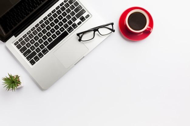 Planta de cactus, taza de café y lentes en la computadora portátil sobre fondo blanco