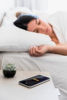 Planta de cactus y teléfono inteligente en mesa cerca de la mujer durmiendo en la cama