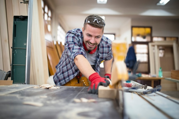 Planta de corte artesano sonriente profesional en máquina circular en taller de carpintería de madera