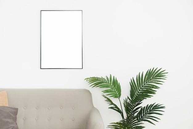 Planta decorativa con marco vacío y sofá