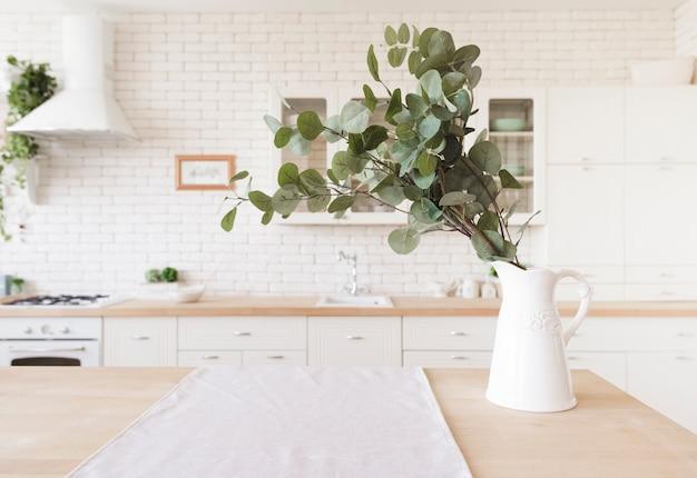 Planta decorativa sobre mesa en luminosa cocina moderna.