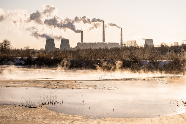 Una planta de energía libera contaminantes en el aire y en un cuerpo de agua. contaminación ambiental