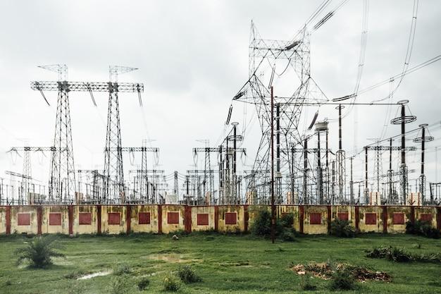 Planta de energía con postes eléctricos de alto voltaje en el lateral del camino a varanasi, india.