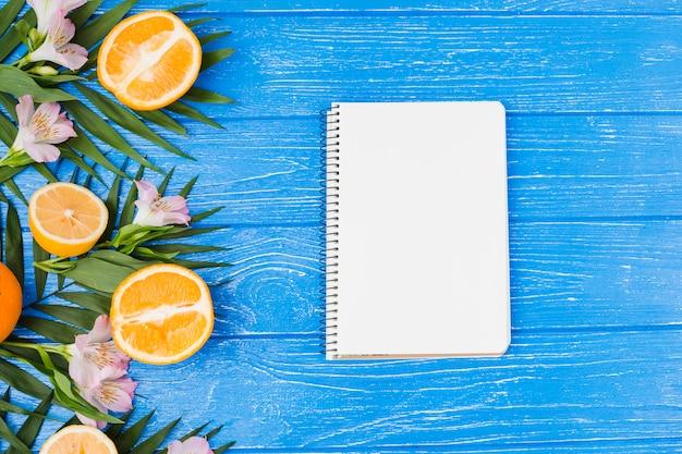 Planta de hojas cerca de naranjas con flores y cuaderno.