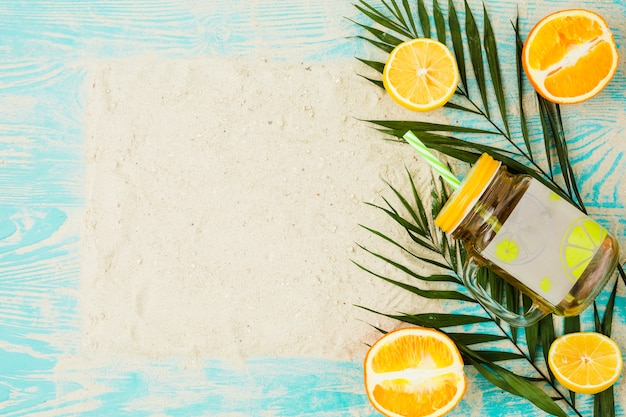 Planta de hojas cerca de vaso de bebida y naranjas con arena a bordo