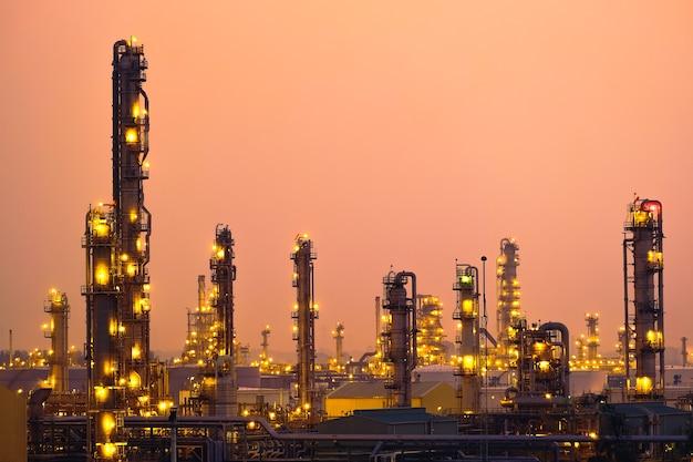 Planta industrial de petróleo y torre de destilación al atardecer