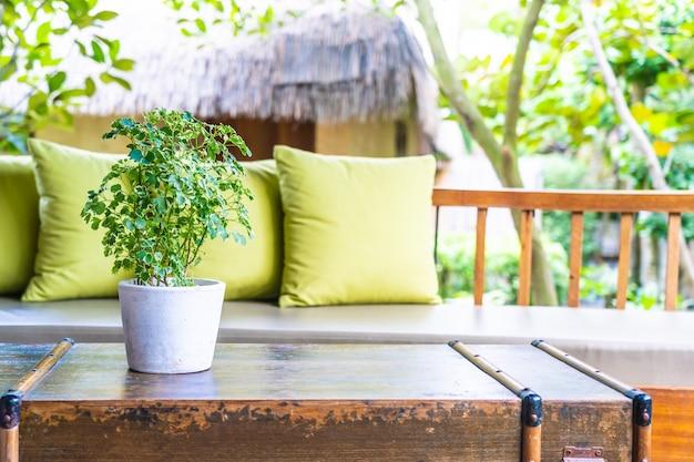 Planta de jarrón sobre decoración de mesa con almohada en sillón