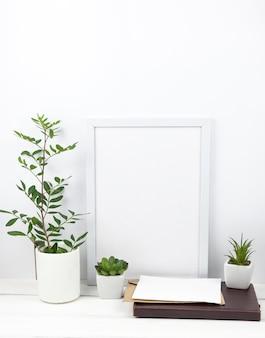 Planta en maceta; marco blanco y diario en casa.