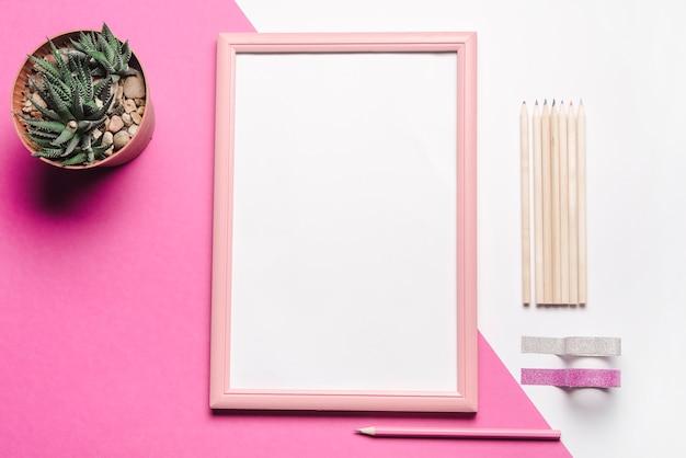 Planta en maceta; marco de fotos blanco; lápices y cintas adhesivas en doble fondo