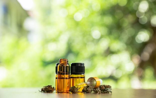 Planta de marihuana con brotes y aceites esenciales en una mesa de madera, concepto de tratamiento de cáncer de hierbas de marihuana.