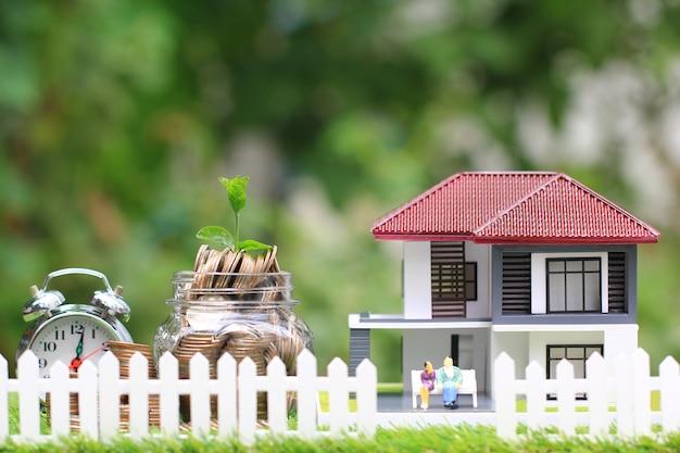 Planta que crece en el dinero de las monedas en una botella de vidrio con una casa modelo y una pareja en miniatura