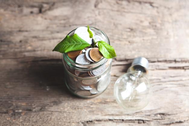 Planta que crece tarro de monedas en la mesa de madera - concepto de crecimiento de la inversión