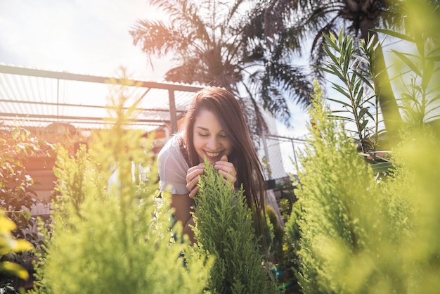 Planta que huele sonriente de la mujer joven en invernadero