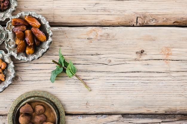 Planta ramita cerca de frutos secos y dulce a bordo.