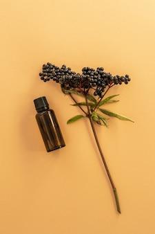 Planta de saúco seco y aceite de esencia sobre superficie beige
