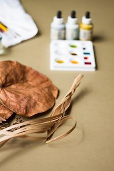 Planta seca con pintura de acuarela en el lugar de trabajo del artista
