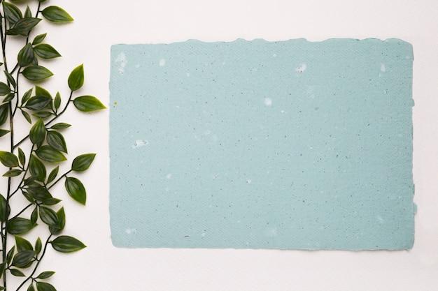 Una planta verde artificial cerca del papel de textura azul en blanco sobre fondo blanco.