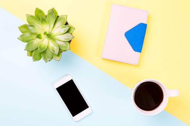 Planta verde en una maceta, taza de café, portátil y moderno teléfono móvil en superficie pastel azul y amarillo.