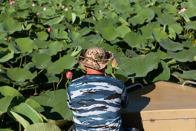 Plantación de flor de loto. el hombre en barco estudia, observa y fotografía el capullo de la flor.