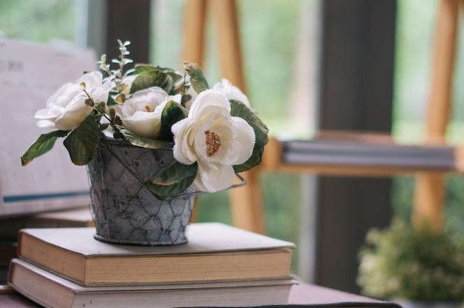 Plantas artificiales y rosas en maceta con fondo borroso