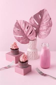 Plantas de monstera y cupcakes rosas.
