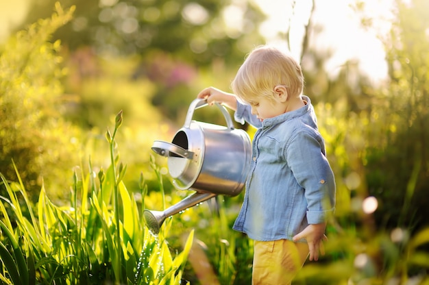 Plantas de riego lindas del niño pequeño en el jardín en el día soleado del verano
