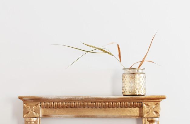 Plantas secas en tarro de oro en estante antiguo sobre fondo blanco.