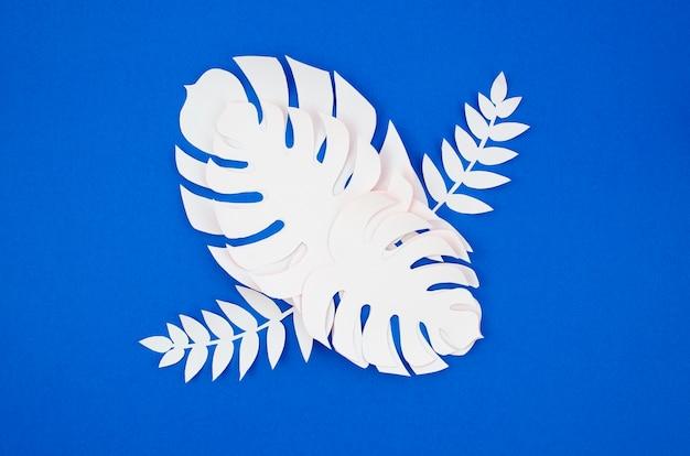 Plantas tropicales en el estilo de papel cortado sobre fondo azul.
