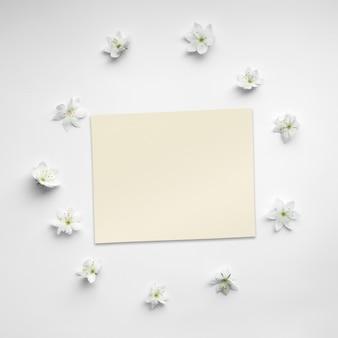 Plantilla hecha de flores blancas florecientes y una tarjeta de papel sobre fondo blanco