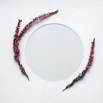 Plantilla hecha de ramitas de brezo floreciente y un marco redondo sobre fondo blanco.