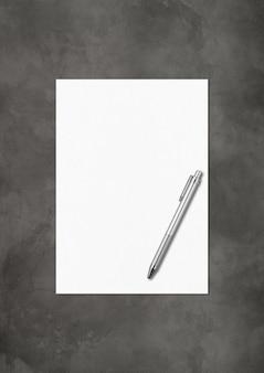Plantilla de maqueta de hoja de papel a4 en blanco y bolígrafo aislada sobre fondo de hormigón oscuro