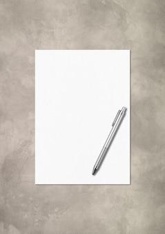 Plantilla de maqueta de hoja de papel a4 en blanco y bolígrafo aislada sobre fondo de hormigón