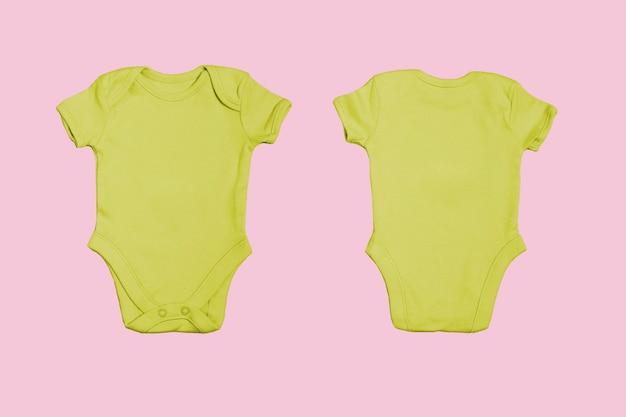 Plantilla de mono de bebé en blanco amarillo, maqueta de primer plano sobre fondo rosa. anverso y reverso. body de bebé, mono para recién nacidos. vista desde arriba