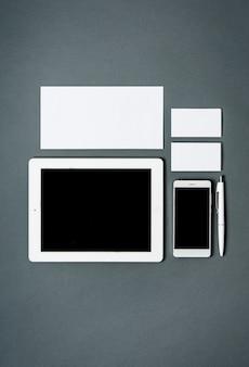 Plantilla de negocios con tarjetas, papeles, tabletas. espacio gris.