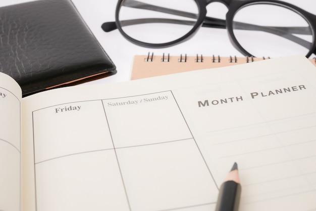 Plantilla de planificación en blanco y la pluma en el escritorio usanos organizador horario vida o planificador de negocios concepto