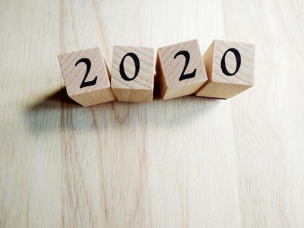 Plantilla de tarjeta de año nuevo de texto 2020 en cubos de madera en madera