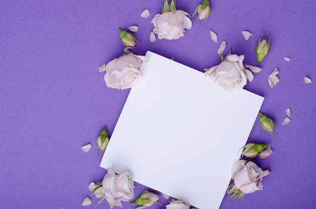 Plantilla de tarjeta de felicitación con hermosas rosas de color lila suave, pétalos y tarjeta blanca para texto.