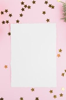 Plantilla de tarjeta de navidad con ramitas de abeto y estrellas doradas y decoración festiva sobre un fondo rosa pastel.
