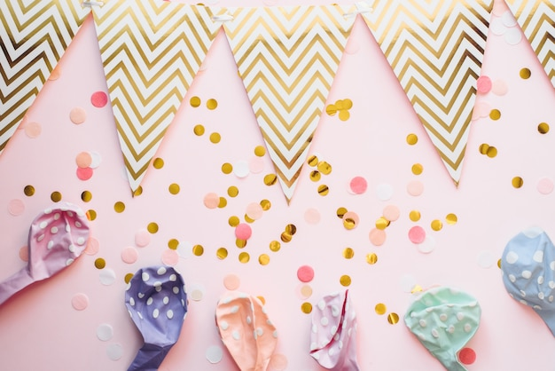 Plantilla para las vacaciones. guirnalda de papel de banderas sobre un fondo rosa con confeti y globos de aire en color pastel. fondo de celebración, cumpleaños