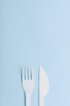 Plástico blanco desechable tenedor y cuchillo sobre un fondo azul.