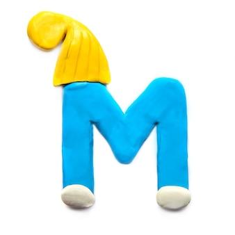 Plastilina azul letra m del alfabeto en invierno sombrero amarillo sobre fondo blanco.