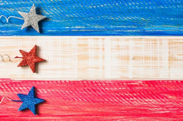 Plata; estrellas decorativas rojas y azules en superficie de madera pintada.