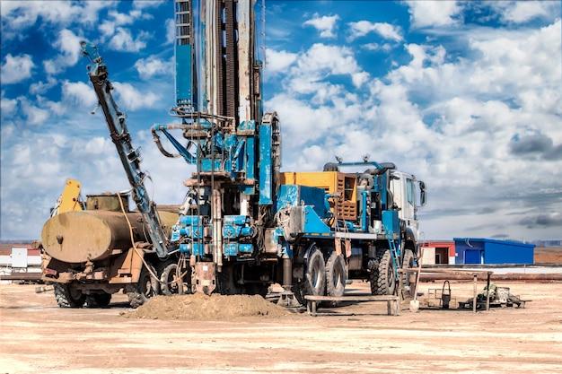 Plataforma de perforación en un campo bajo un cielo nublado azul. perforación de pozos profundos. exploración geológica. exploración de minerales.