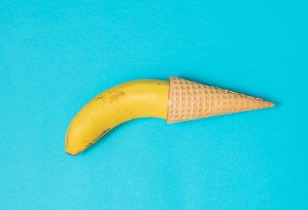 Plátano amarillo en un cono de waffle. problemas masculinos, impotencia, concepto de mala erección